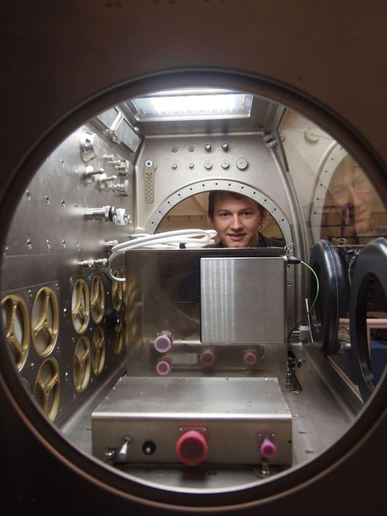 Aaron Kemmer stares through the windows of the Microgravity Science Glovebox with the Zero-G 3D Printer enclosed